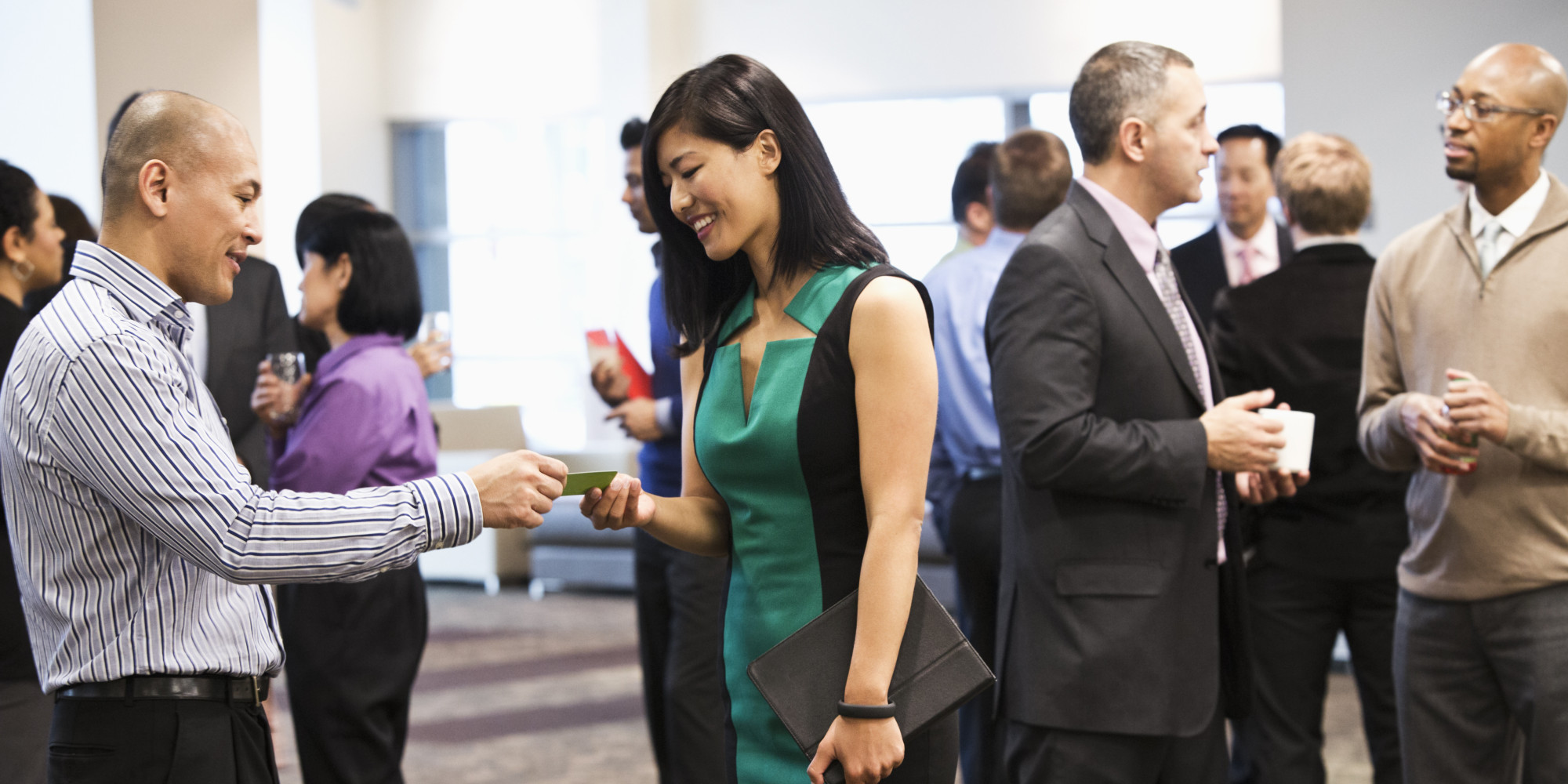 professionals trading business cards at a trade show